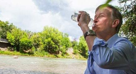 Gov. John Hickenlooper drinks from Animas River
