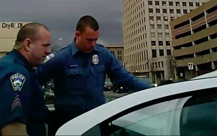 Sergeant Clayton Blackwell and Officer Dustin Canaan look at their unfamiliar detainee.